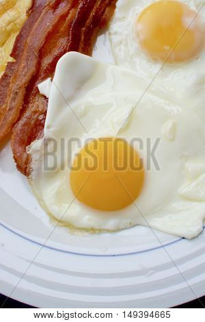 Cooked breakfast with eggs, streaky bacon and grilled cheese