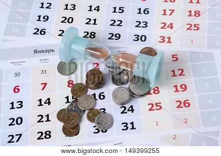 Hourglass on calendar sheets lie near the small coins
