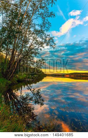Bright sunset on forest lake in autumn