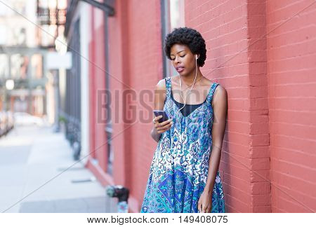 Portrait of young African American woman listening to music and texting on city street. Photographed in Soho NYC.