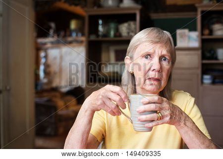 Worried Senior Woman Holding Coffee Cup