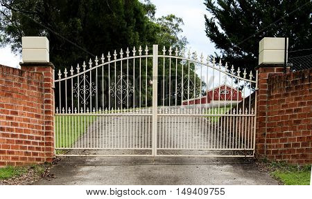 Wrought iron metal driveway entrance gates set in brick fence