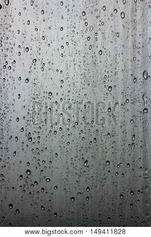 Glass window with raindrops running down on a bleak grey sky.