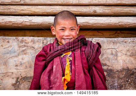 The little boy smiling of buddhist novice monks are praying in Boudhanath monastery