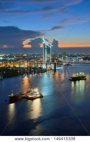 Beautiful nightfall of Chao Phraya River, Many cargo ships docked in the middle river near the Rama 9 Bridge.
