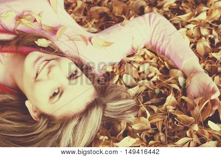 Beautiful smiling woman playing in autumn leaves
