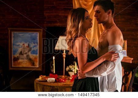 Couple in love dancing and kissing into luxary restaraunt. Romantic evening interior for loving couple. A lot of pictures in room.