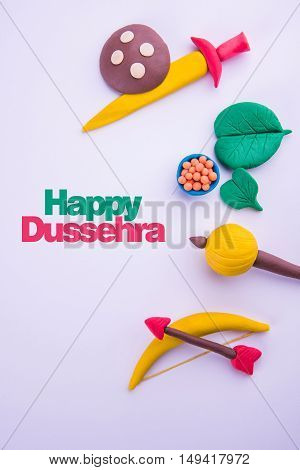 happy dussehra greeting card made using a photograph of colourful clay models of ancient indian armour used in Ramayana and Mahabharata like bow and arrow, sword and shield, gada or gadda, apta leaf poster