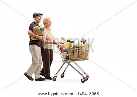 Full length profile shot of a mature couple pushing a shopping cart full of groceries isolated on white background