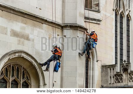 Two construction workers hanging on ropes and harnesses repairing the facade of Westminster Abbey in London. One of them is watching his mobile phone.