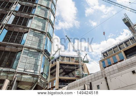 LONDON UK - AUGUST 21 2015: Cranes on a building under construction in London a blue sky day. Low angle view