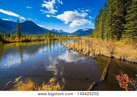 Shallow Lake Vermilion is surrounded by mountains and forests. Indian summer in the Rocky Mountains of Canada