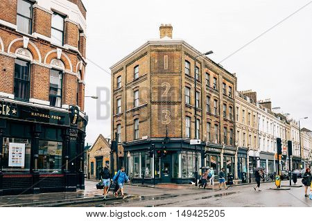 LONDON UK - AUGUST 23 2015: People crossing Bethnal Green Road a rainy day. It´s located in Shoreditch near Brick Lane Market.