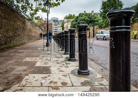 LONDON UK - AUGUST 24 2015: Row of bollards in a street of London low angle view on a cloudy day