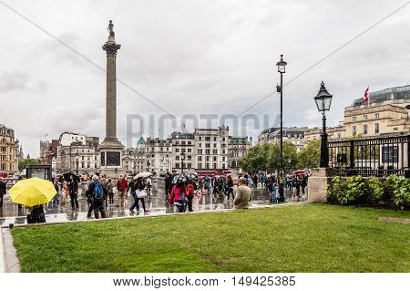 LONDON UK - AUGUST 24 2015: Crowd in Trafalgar Square a rainy day of summer. Trafalgar Square is a public square thatcommemorates the Battle of Trafalgar