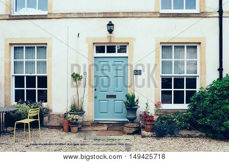 Cirencester UK - August 18 2015: English town house entrance with front courtyard and a painted closed door