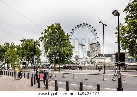 London UK - August 18 2015: London cityscape from Victoria Embankment with London Eye attraction on background a cloudy day. The London Eye is a giant Ferris wheel on the South Bank of the River Thames in London.