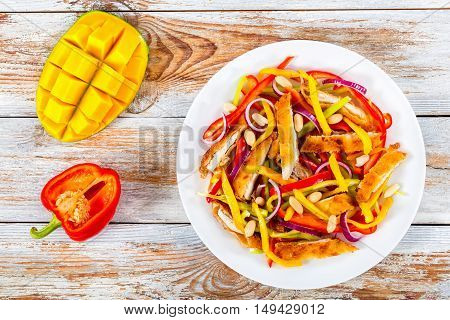 bread crumbed chicken meat mango peanuts bell pepper red onion salad on white dish with half of mango cutting in cubes and bell pepper on white peeling paint boards view from above