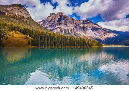The concept of eco-tourism and active recreation. Charming mountain lake. The smooth turquoise water in the wooded mountains. Sunny day in autumn