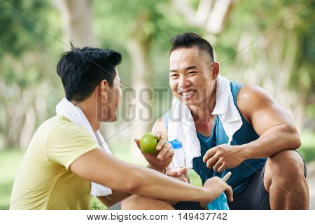 Vietnamese sportsmen having apples and water after training