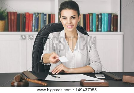 Beautiful young woman giving business card in modern office