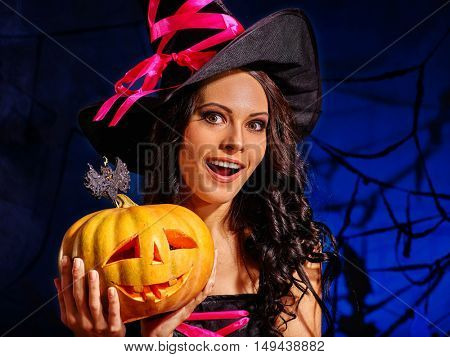 Happy young woman witch wearing witch hat holding big pumpkin.