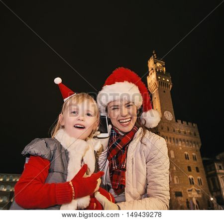 Mother And Child In Christmas Hats In Florence Using Mobile