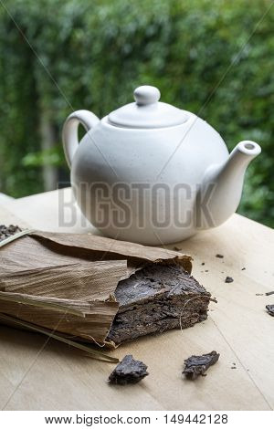 Natural tea with white teakettle on the wooden table and green leaves as background