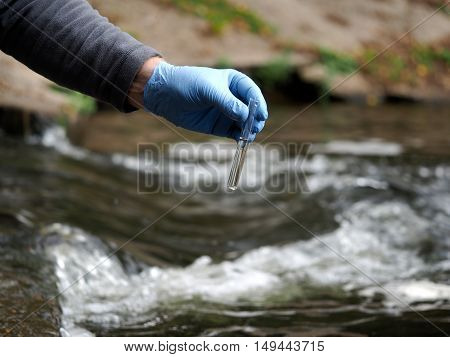 Water Sample. Gloved Hand Into The Water Collecting Tube. Analysis Of Water Purity, Environment, Eco