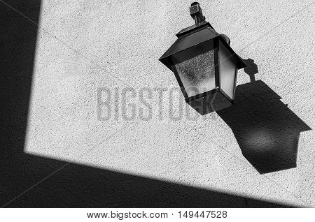 Lamppost on the wall with shadows and textures - Black and White
