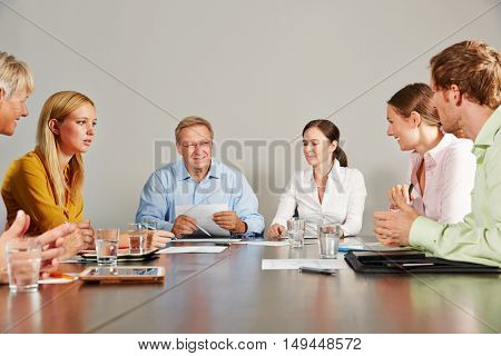 Buisiness team with CEO talking in a meeting in a conference room