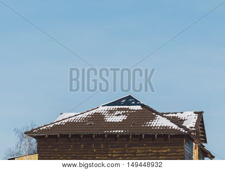 Wood house in village with roof in snow in winter time