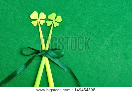 A four leaf clovers on a sticks tied together with a green bow isolated on a green background for St. Patrick's day