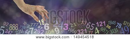 Numerology Wide Bokeh Website Banner - dark multicolored bokeh background with transparent numbers randomly placed along the bottom and a female hand choosing the number 18