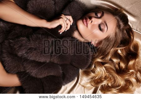 fashion studio photo of gorgeous woman with blond hair in luxurious dress and fur coat