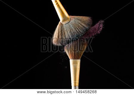 Make-up brushes with pink powder isolated on black background