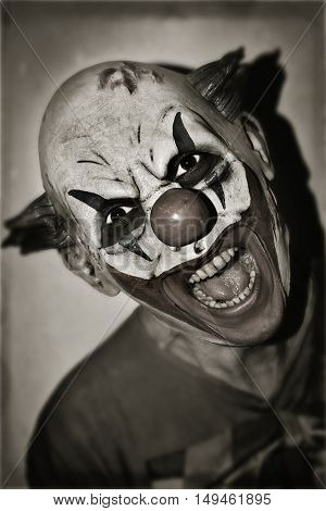 portrait of a scary evil clown, in sepia toning, with a retro effect