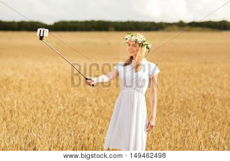 technology, summer holidays, vacation and people concept - smiling young woman in wreath of flowers taking picture by smartphone selfie stick on cereal field