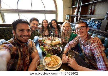people, leisure, friendship and technology concept - happy friends taking selfie, drinking beer and eating snacks at bar or pub