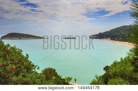 Summertime.Gargano coast: Baia di Campi beach,Vieste-(Apulia) ITALY-The pebbly beach is a picturesque bay sheltered the south  by the Campi rock,framed by olive trees and pinewoods.