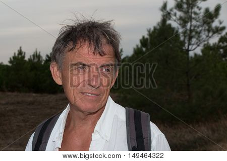 Happy attractive handsome senior man outside with a back pack smiling