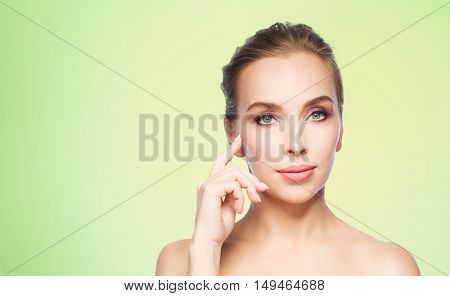 beauty, people and plastic surgery concept - beautiful young woman showing her cheekbone over green background