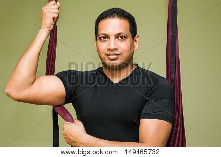 Man making aerial yoga exercises indoor aerial yoga