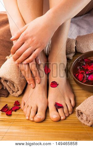 Beautiful female feet and hands, spa salon, pedicure and manicure procedure with petals of red rose flower