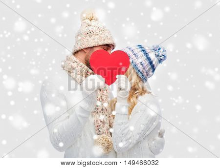 love, valentines day, couple, christmas and people concept - smiling man and woman in winter hats and scarf hiding behind red paper heart shape