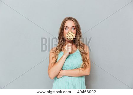Funny cute young woman covered her mouth with lollipop over gray background
