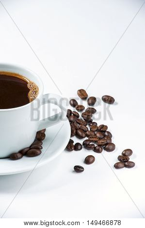 Cup of coffee with coffee beans on white background. Cropped shot.