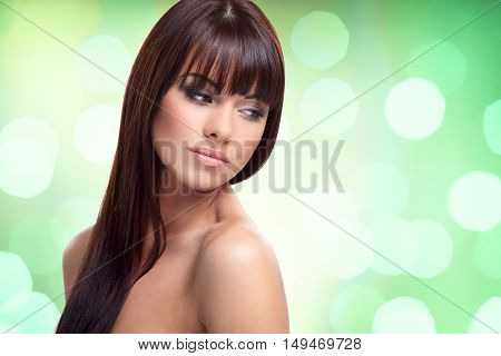 Portrait of beautiful female model on sparkling green background