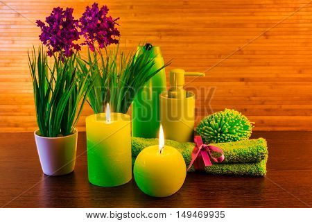 Green spa bath products concept with candles flowers towel