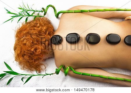 Beautiful woman with curly hair relaxing with hot stones on body and green bamboo on white towel
